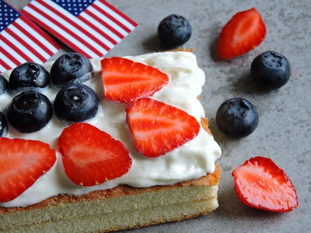 Bizcocho el 4 de julio con la bandera estadounidense. bizcocho con crema, fresa y arándano. postre al estilo del día de la independencia. dulces en colores patrios.