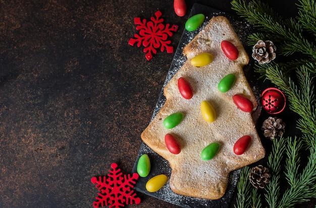 Bizcocho casero forma de árbol de navidad, decorado con dulces multicolores dulces.