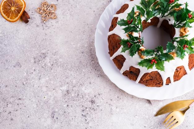 Bizcocho de chocolate negro casero de navidad decorado con ramas de acebo en piedra