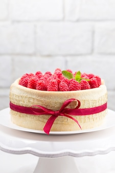 Bizcocho de cumpleaños con cinta decorada con frambuesas y lazo sobre un soporte de pastel blanco