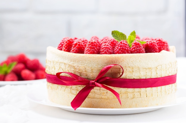 Bizcocho de cumpleaños con frambuesas decorado con cinta blanca y lazo sobre un fondo claro