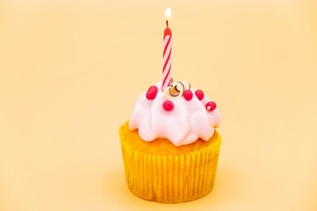 Bizcocho de cumpleaños sabroso con vela, sobre fondo naranja.