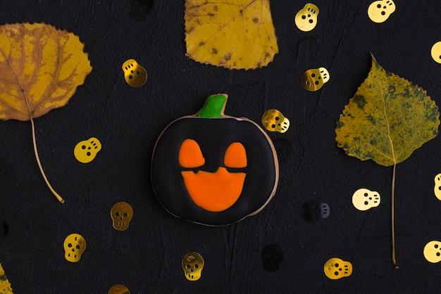 Bizcocho de halloween, hojas secas y cráneos ornamentales