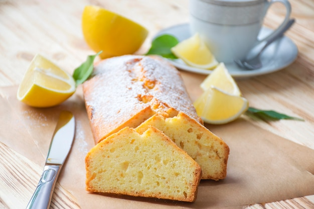 Bizcocho de limón húmedo sobre pergamino sobre fondo de madera rústica con rodajas de limón, cuchillo y taza de té en un plato.