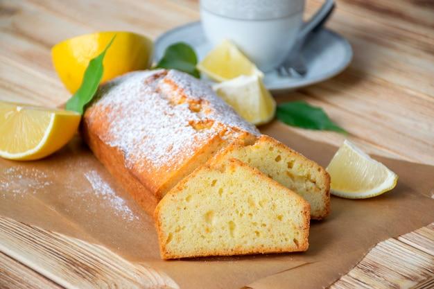 Bizcocho de limón húmedo sobre pergamino sobre fondo de madera rústica con rodajas de limón y una taza de té en la placa.