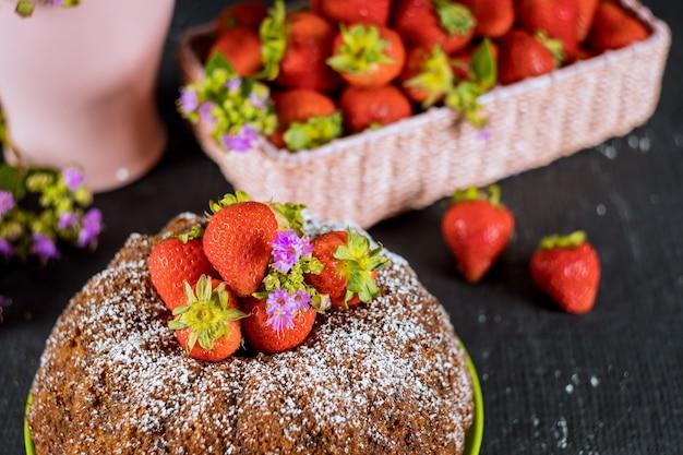 Bizcocho de vainilla y cesta con fresas frescas.