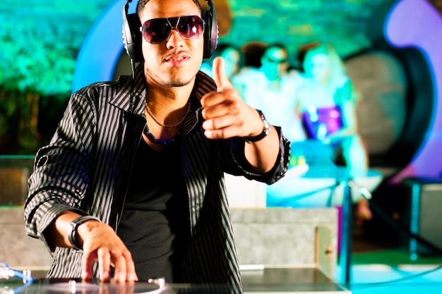 Black dj en un club en el tocadiscos, en el fondo la multitud está animando