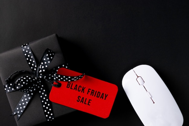 Black friday o compras online. regalos negros, etiqueta roja y ratón con espacio de copia para anunciante.