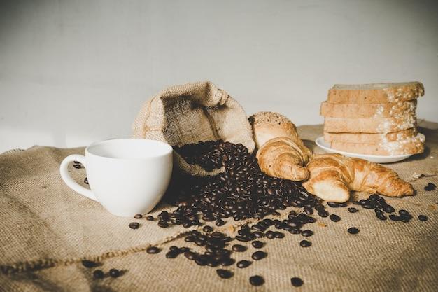 Blanca taza de café con croissant y granos de café