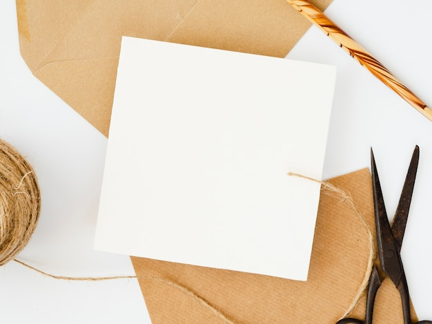 Blanco en blanco sobre sobres marrones con un lápiz de madera sobre un fondo blanco.