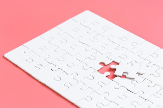Blanco conectado piezas de rompecabezas en la pared de color rojo pastel