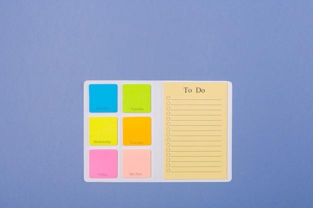 En blanco para hacer la lista para la semana sobre fondo morado claro, plano. copia espacio espacio libre. calendario. calendario.