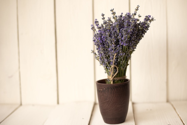 En blanco hay un vaso de madera marrón con un fragante ramo de lavanda oliva.