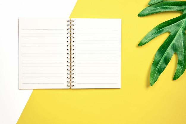 Blanco de la libreta de la pantalla en blanco colocado sobre fondo amarillo pastel