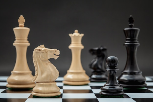 Blanco y negro rey y caballero de la configuración de ajedrez en el fondo oscuro.