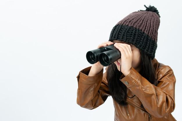Con un blanco, el niño está buscando algo con binoculares.