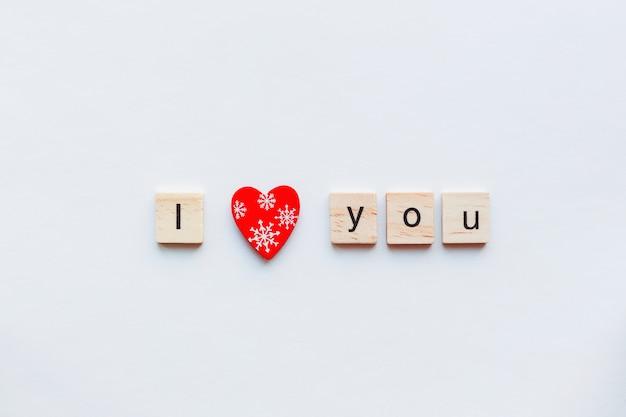 Blanco con palabras de madera te amo y corazón rojo, símbolo del amor.