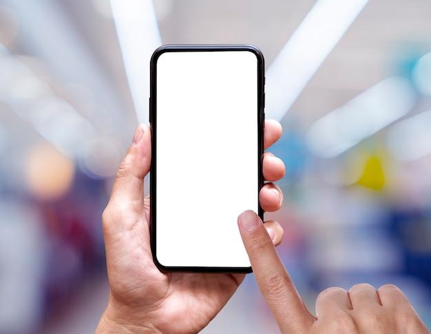 En blanco de la pantalla del teléfono móvil en el fondo del centro comercial