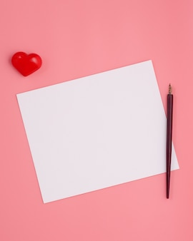 En blanco con pluma de tinta y corazón sobre fondo rosa