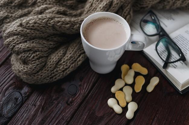 Blanco taza de cacao en una vieja mesa de madera con un libro entretenido y gafas de lectura.