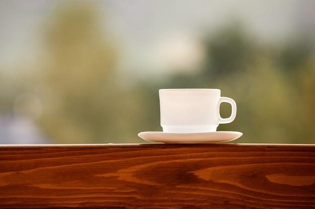 Blanco taza de café sobre una mesa de madera. taza de té blanco en la mesa de madera sobre fondo verde. jardín y taza de café. lugar para texto