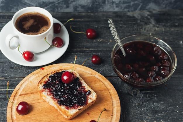 Blanco taza de café y tostadas con mermelada de cerezas en plato blanco sobre mesa negra