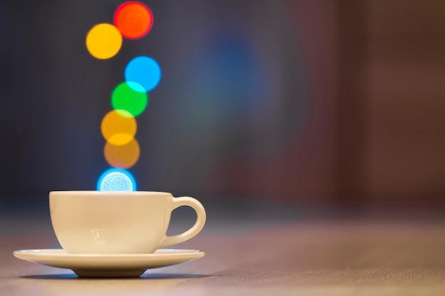 Blanco taza de café con vapor colorido bokeh