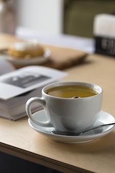 Blanco taza de té y libro sobre una mesa en un café.