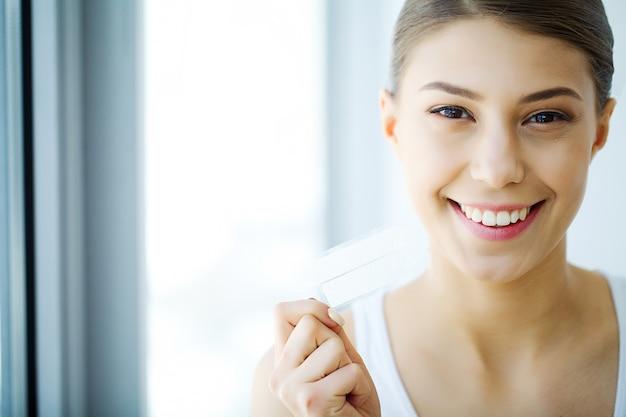 Blanqueamiento de dientes, hermosa mujer sonriente con tira de blanqueamiento,