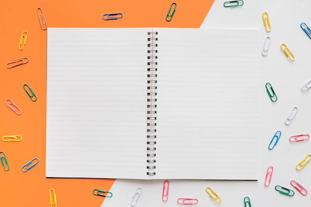 Bloc de notas espiral abierto rodeado de varios alfileres de colores sobre fondo colorido