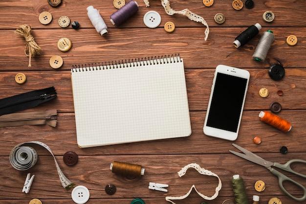 Bloc de notas y teléfono móvil rodeado de accesorios de costura en el fondo de madera