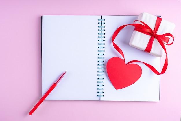 Bloc de notas abierto en blanco blanco, bolígrafo rojo, caja de regalo con cinta roja y forma de corazón de papel rosa