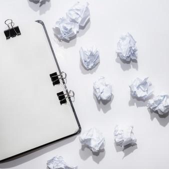 Bloc de notas abierto en blanco con papeles arrugados