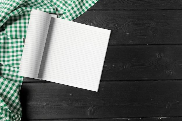 Bloc de notas abierto en blanco sobre fondo de madera con un trozo de tela