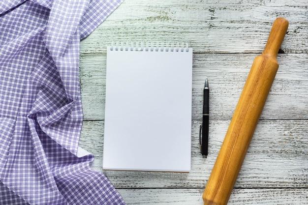 Bloc de notas abierto con bolígrafo, servilleta y rodillo