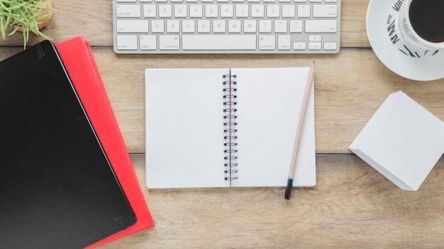 Bloc de notas abierto y papelería cerca del teclado y la taza de café