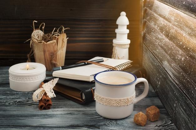 Bloc de notas abierto, vela, lápiz y café.