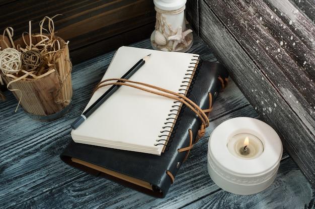 Bloc de notas abierto, vela, lápiz y decoración.
