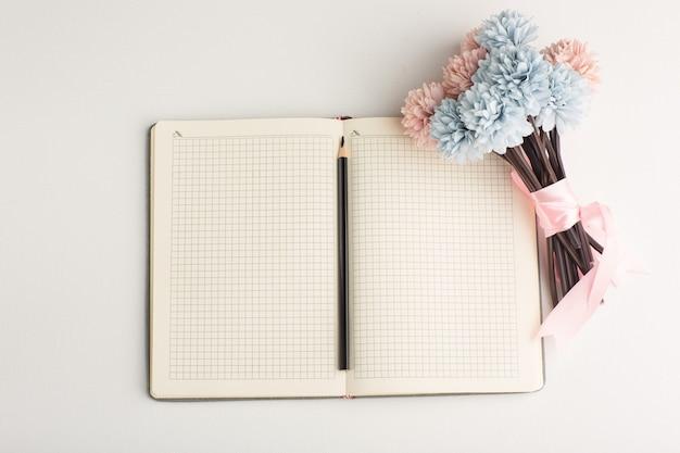Bloc de notas abierto vista superior con flor y lápiz sobre superficie blanca
