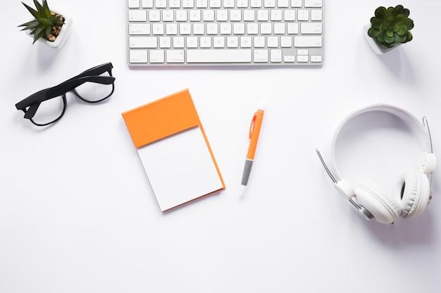 Bloc de notas adhesivo en blanco; los anteojos; bolígrafo; planta de cactus; auriculares y teclado en el escritorio blanco
