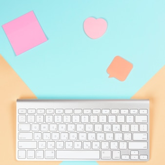 Bloc de notas adhesivo; forma de corazón y bocadillo con teclado inalámbrico blanco sobre fondo dual