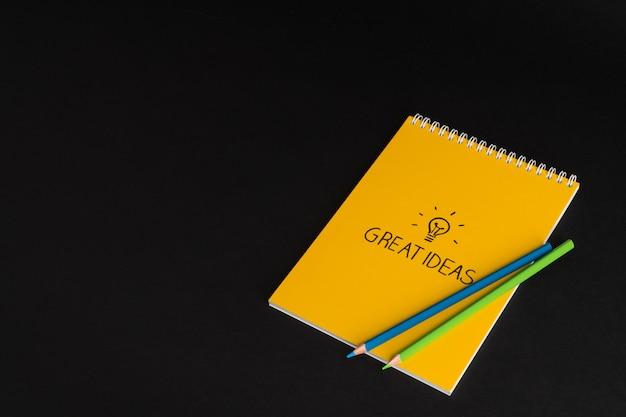 Bloc de notas amarillo con lápices de colores sobre fondo negro, aislado. de vuelta a la escuela. grandes ideas