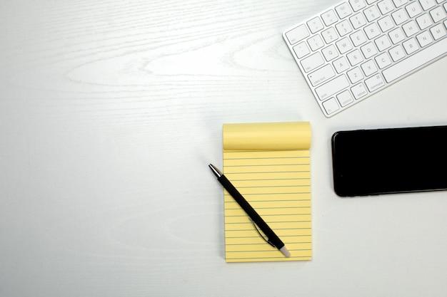 Bloc de notas amarillo teclado y teléfono inteligente