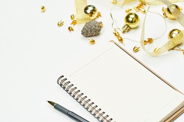Bloc de notas en blanco con adornos navideños. bloc de notas para escribir nuevas resoluciones para el nuevo año. planificación de las vacaciones de navidad.