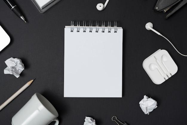 Bloc de notas blanco en blanco rodeado de taza vacía; papel arrugado; bolígrafo; auricular sobre fondo negro