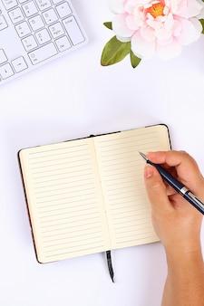 Un bloc de notas blanco en blanco sobre un escritorio blanco