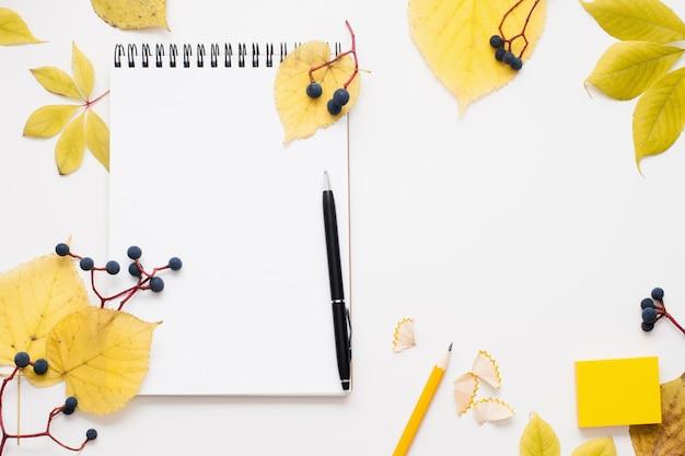 Bloc de notas en blanco con bolígrafo en marco de hojas de otoño