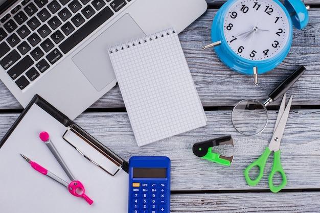 Bloc de notas en blanco para copiar espacio y accesorios para estudiar. pc portátil plano laico con calculadora y reloj en la mesa de madera blanca.