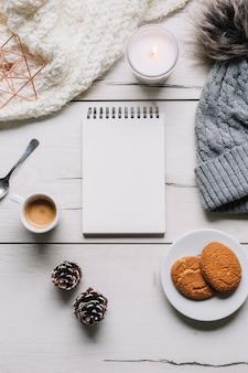 Bloc de notas en blanco con galletas en la mesa