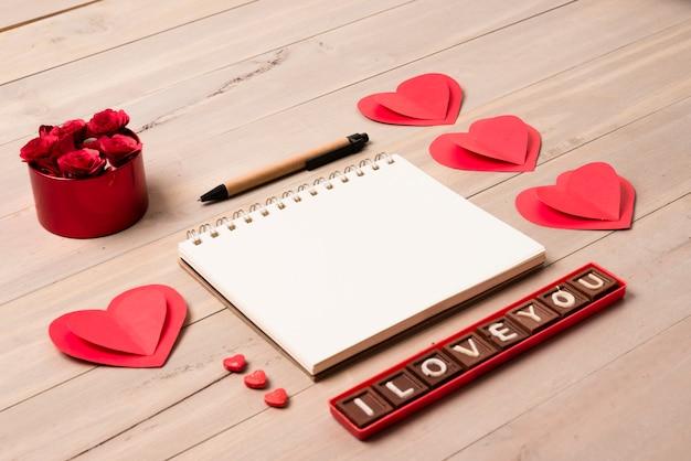 Bloc de notas en blanco con la inscripción te amo en la mesa